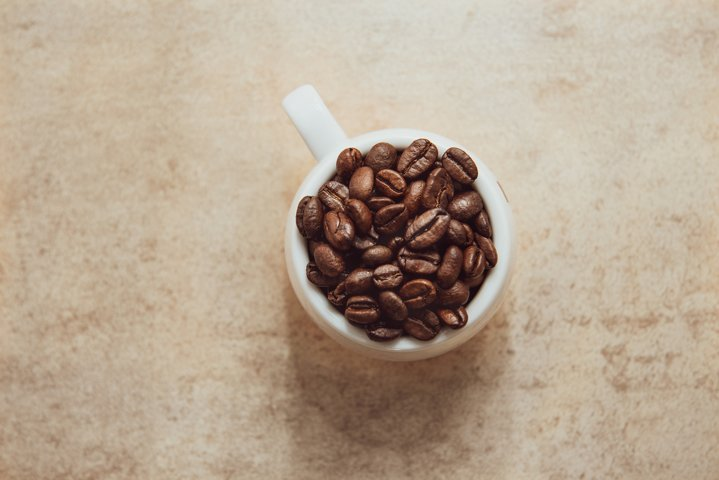 Cup of coffee full of coffee beans