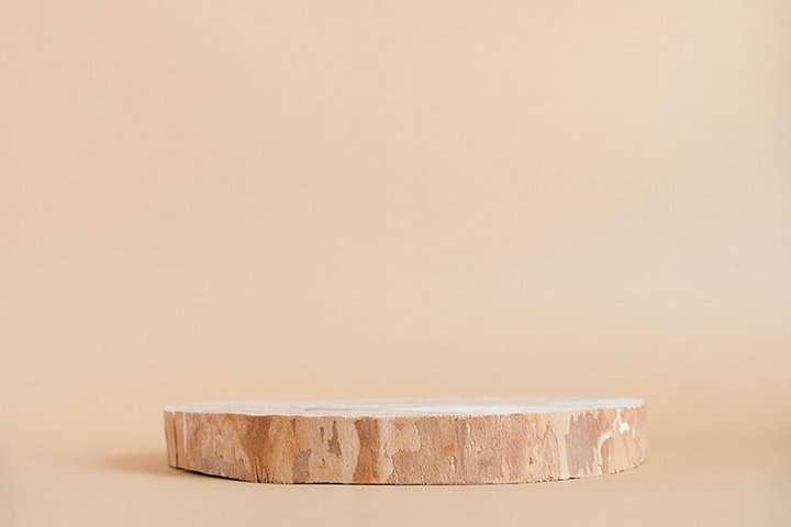 Round wooden saw cut cylinder shape on beige background