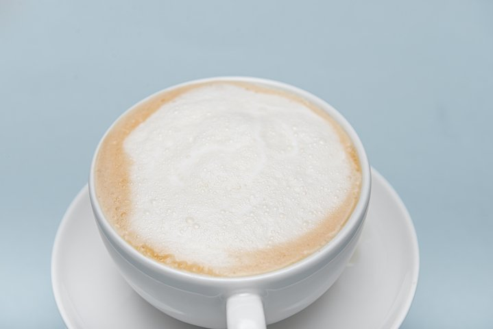 part of white cappuccino cup isolated on a blue background