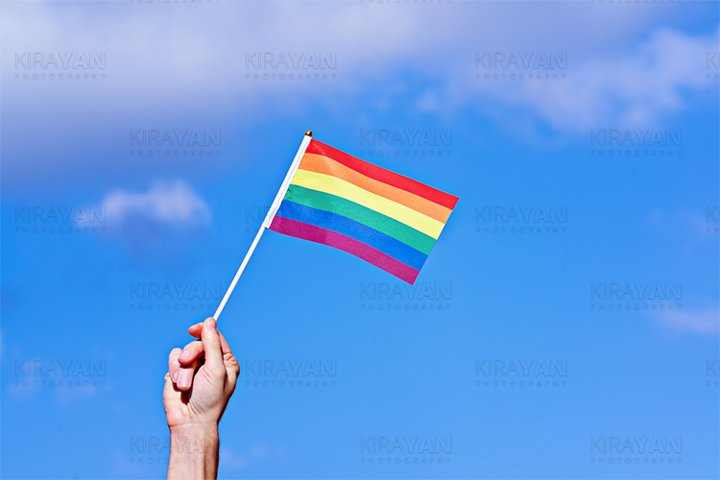 Raised hand with waving LGBTQ rainbow flag against blue sky