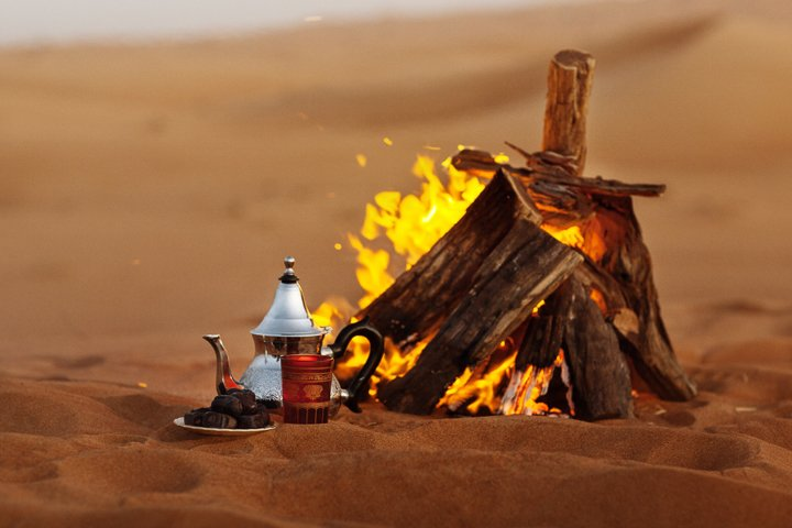Dates, teapot, cup with tea near the fire in the desert