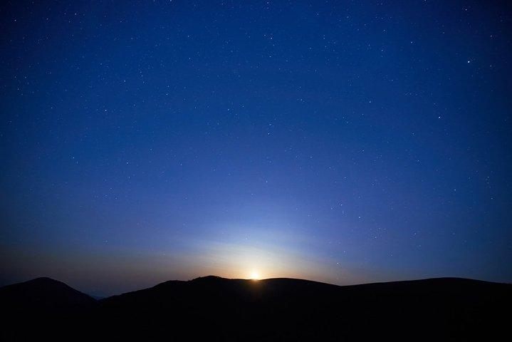 Blue dark night sky with many stars. Moon rising