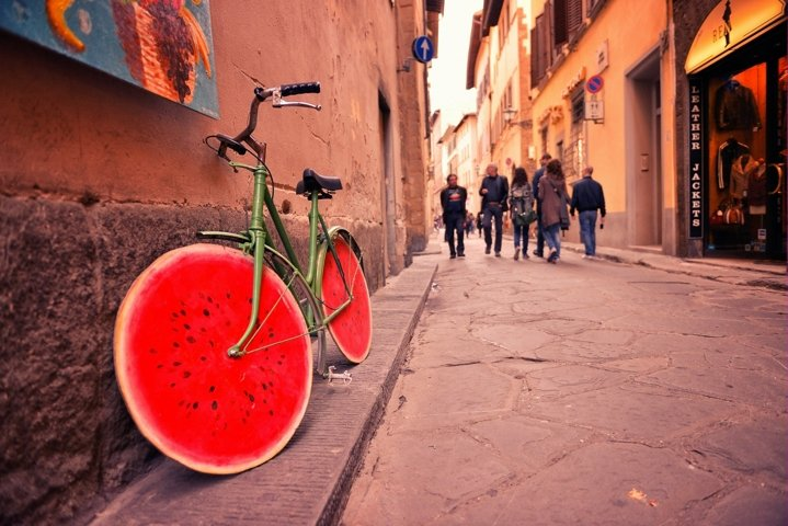Old bicycle with watermelon wheels near the wall