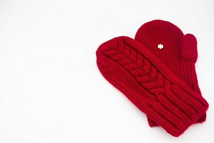 Knitted red mittens with white snowflake