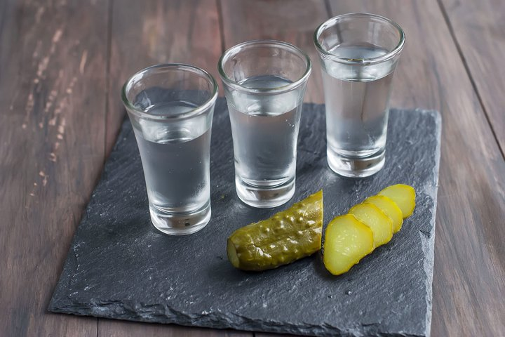 small glass with Russian vodka and salt cucumber