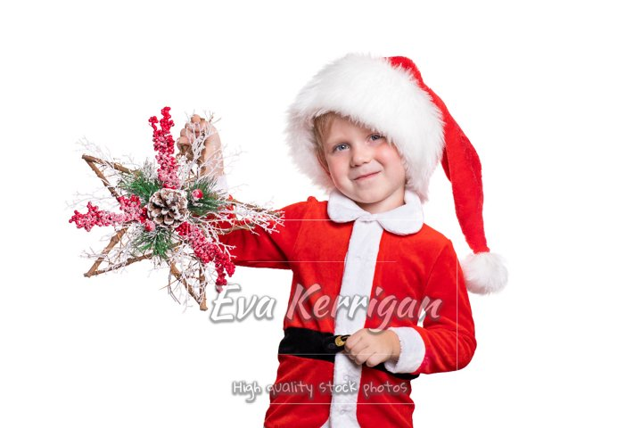 A child boy in a suit and a Santa Claus hat holds a wooden.