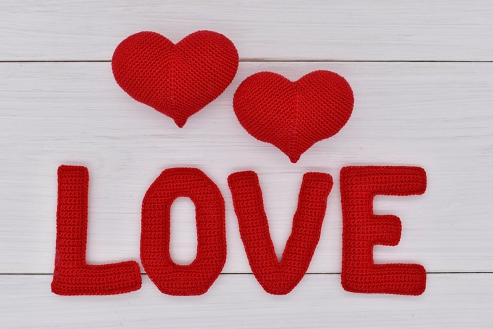 Red knitted hearts and the word love on white wooden boards.