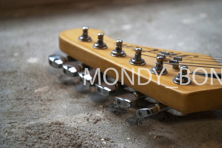 Close-up wooden guitar neck with knobs