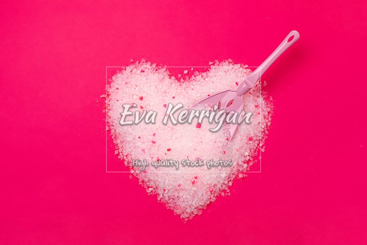 Cat litter, heart shaped bright pink background.
