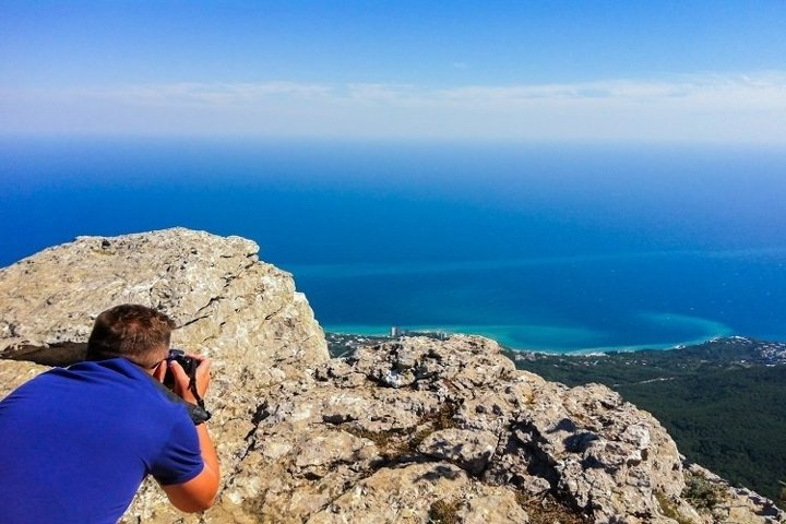 Photographer on the mountain takes a view
