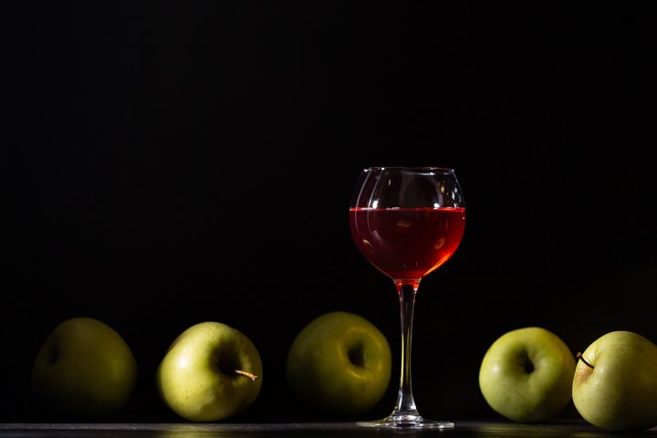 A glass of red fruit wine. Apples fresh crop, still life.