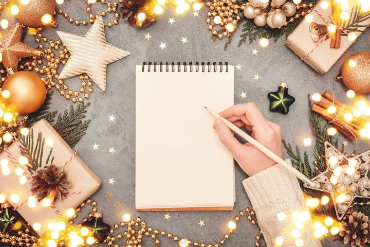 Notepad and writing female hand with holiday decorations.