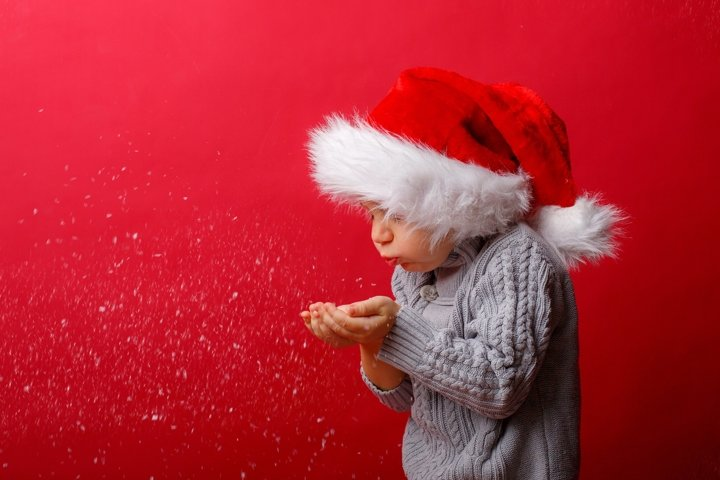 a boy in a Santa hat on a red background blows on the snow