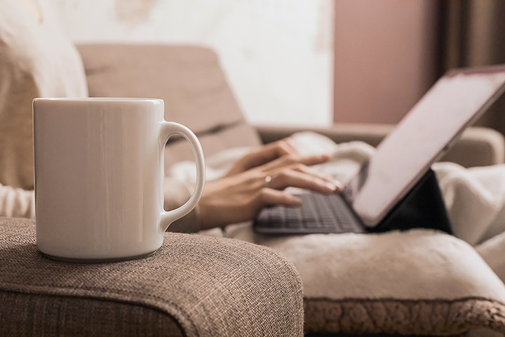 A white mug stands on the arm of a brown sofa