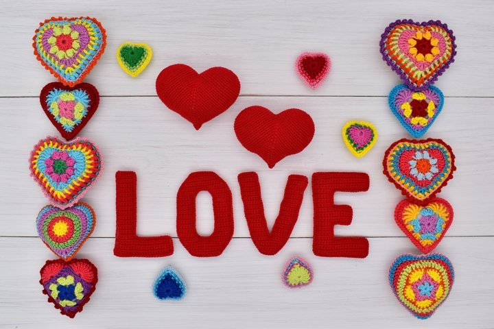 Knitted hearts and the word love on white wooden boards.