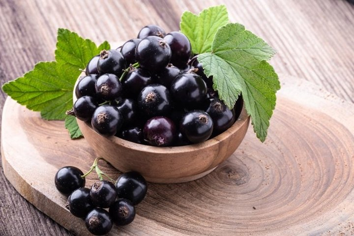Black currant with leaves on rustic old wooden table.