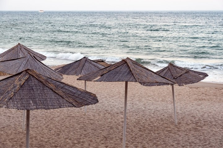 Seascape with beach umbrellas near sea surf. Photo Wall Art