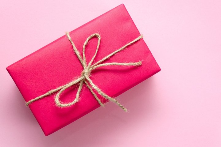 Pink gift box tied with twine on a light pink background
