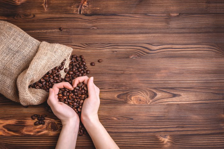 Roasted coffee beans waking up from a jute coffee bag.
