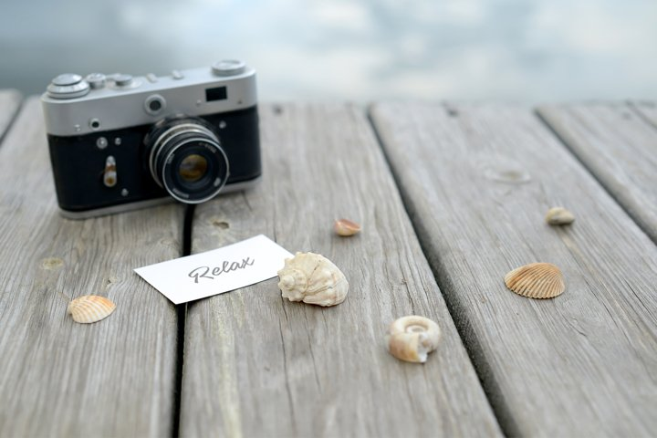 Wooden Background with a retro camera and seashells