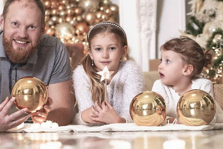 Happy family in Christmas night near christmas tree