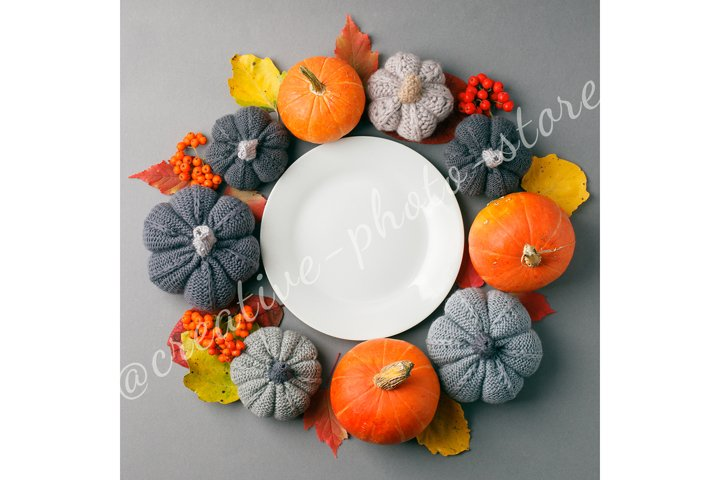 White plate with autumnal decor on gray background