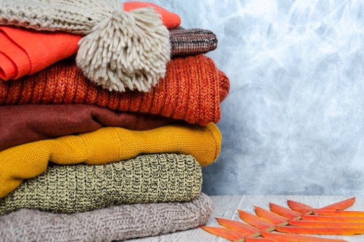 Stack of folded warm knitted womens sweaters, scarf, hat