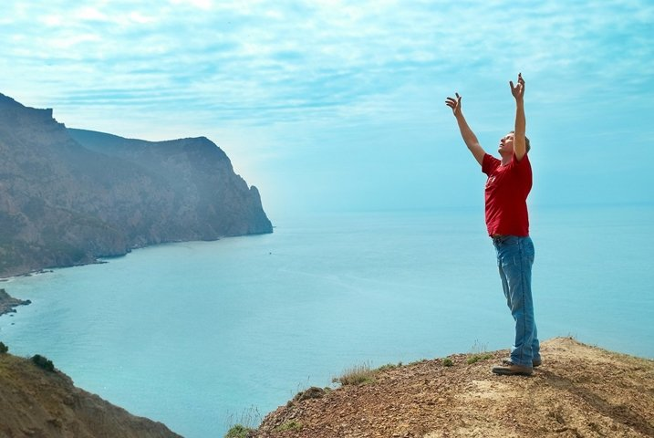 Happy man standing on the cliff with hands up