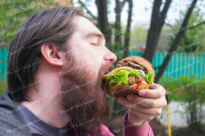 Bearded man eat burger