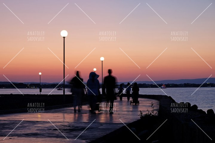 Silhouettes of people walking near sea on sunset background