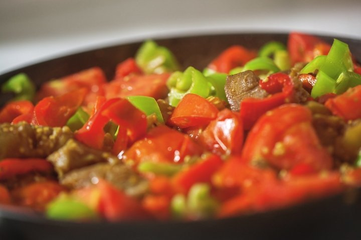 Served dish with meat, tomatoes and pepper