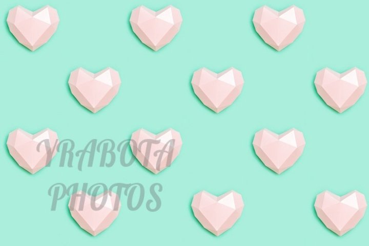 Seamless pattern from pink paper hearts on mint color paper