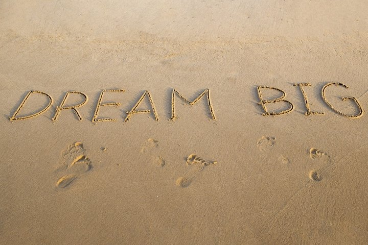 Handwritten DREAM BIG on a sandy sea beach