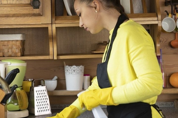 Pretty young girl in black apron in kitchen
