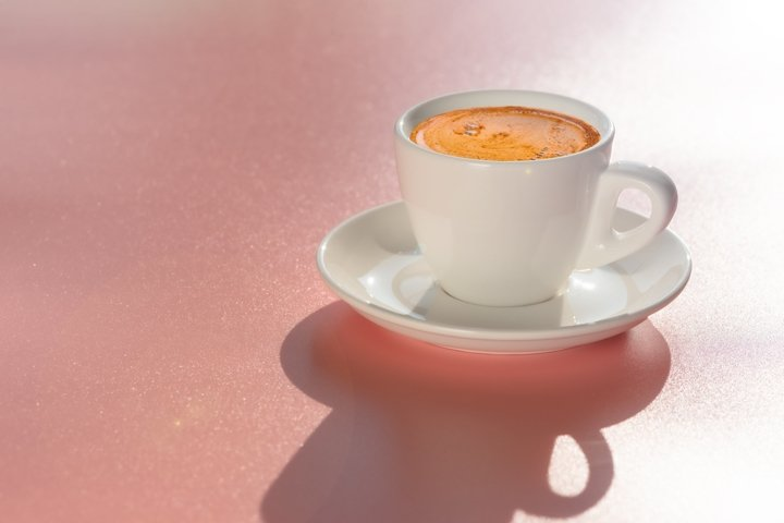 White cup of coffee on pink background in soft morning light