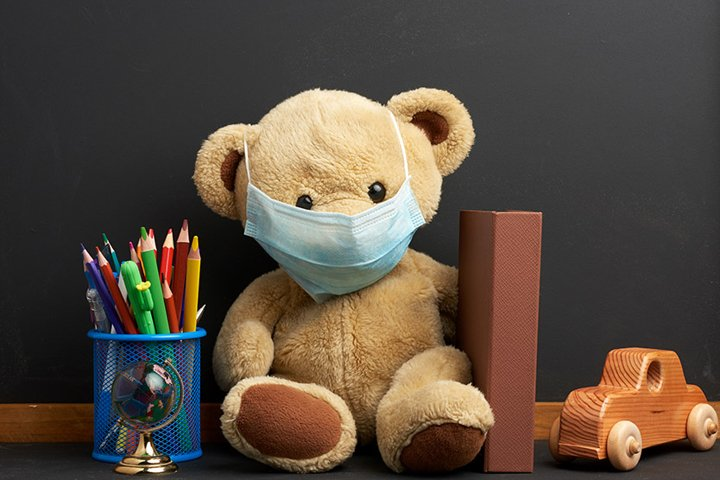 brown teddy bear sitting in a disposable medical mask