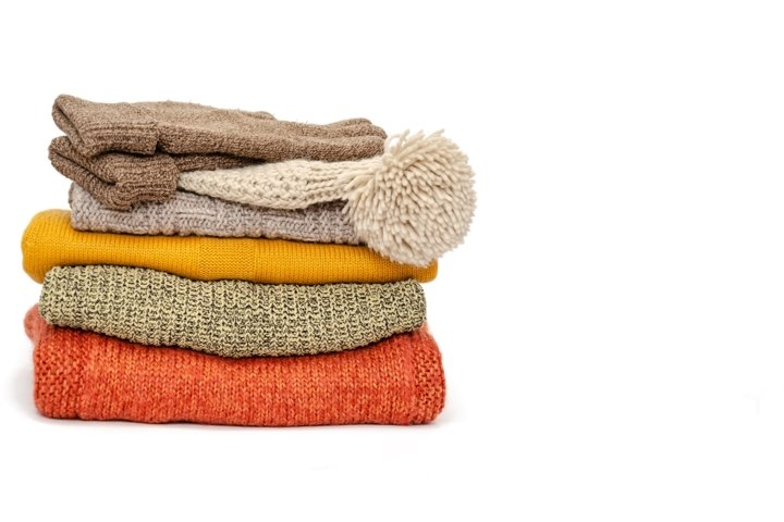 Stack of folded knitted warm women sweaters, hat and gloves
