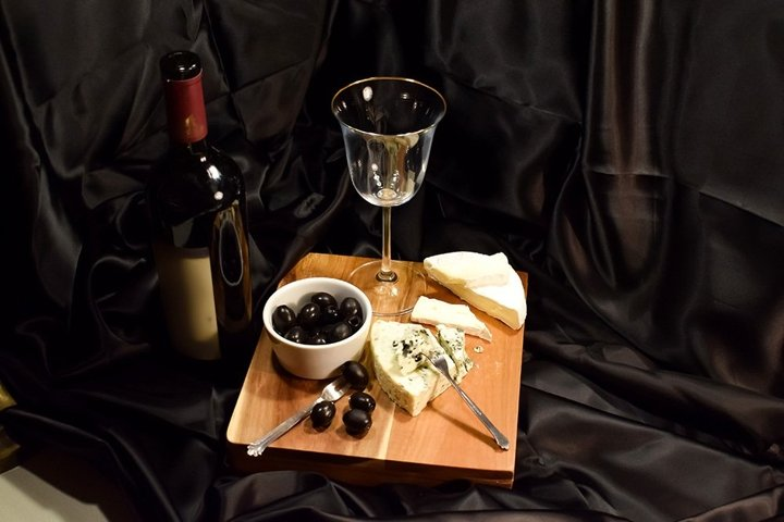 Red wine, French cheese on a black background