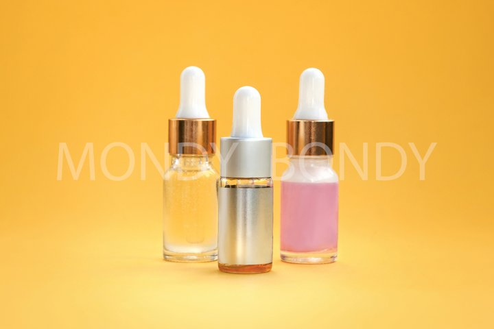 Three bottles of cosmetic oil, serum skin care products