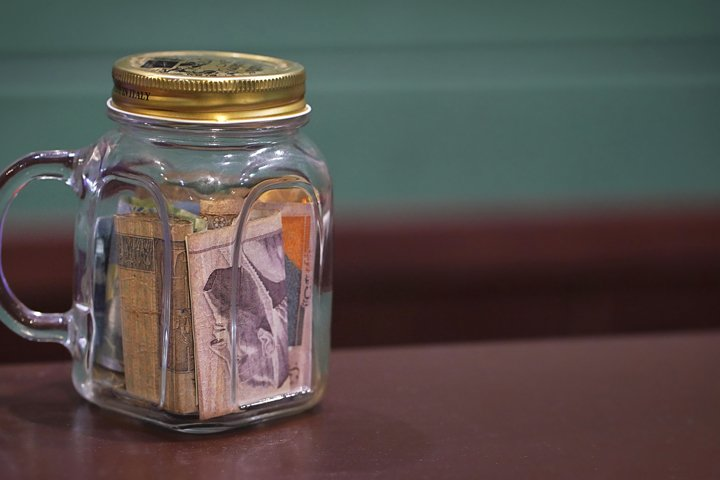 Tipping in a glass jar on a bar counter top