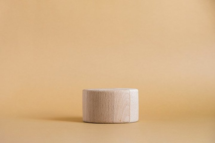 Wooden round cylinder shape on beige background.