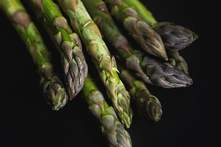Fresh green asparagus spears on black background.