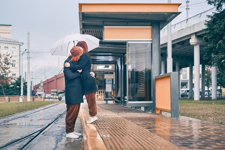 Man woman cuddling in the rain. young couple together under