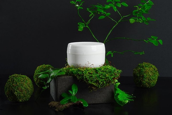 Moisturizing cream jar and greenery. Natural cosmetic