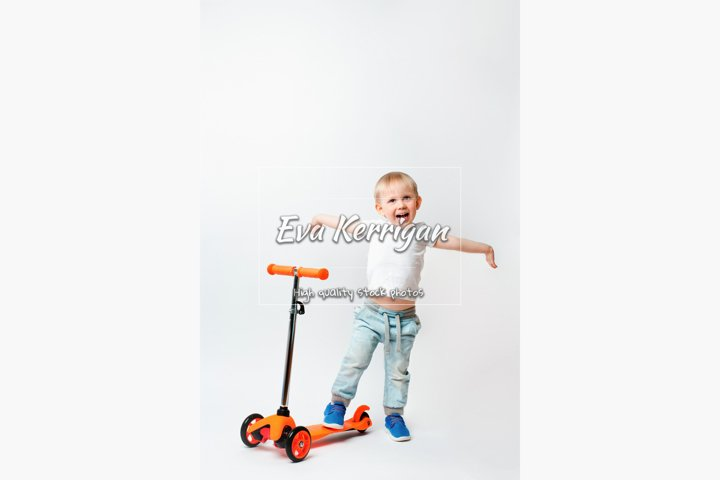 Joyful child, raised his hands in awe of the scooters gift.
