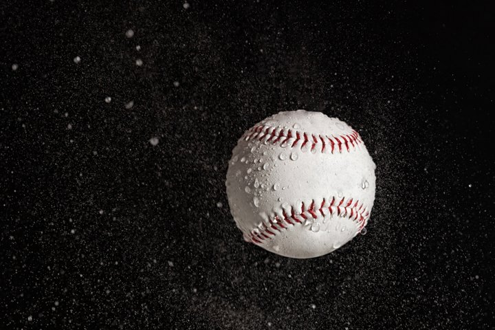 Baseball ball flying in the rain on a black background.