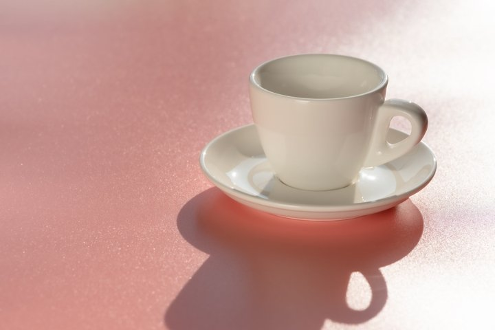 Empty clean coffee cup on pink background. Minimal style