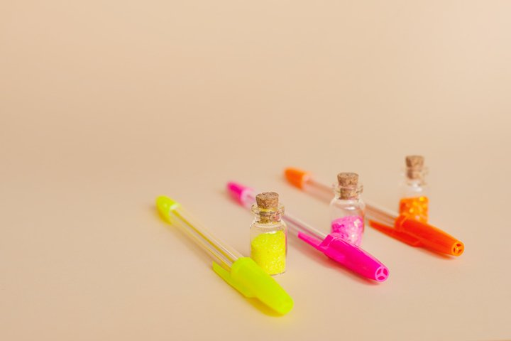 Multi-colored sparkles in bottles and bright neon pens