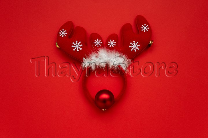 Christmas reindeer made from decorations on red background