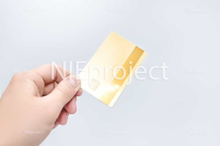 Man holding gold credit card in hand on white background